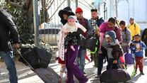 Central American families stand in line, waiting to present themselves to U.S. immigration authorities at the U.S.-Mexico border near Ciudad Juarez, Mexico.