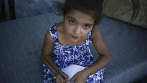 A young Syrian refugee girl writes in a notebook.