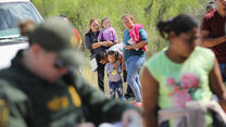Central American asylum seekers wait as a U.S. Border Patrol agents take groups of them into custody on June 12, 2018 near McAllen, Texas. photo by John Moore/Getty Images