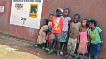 Children stand and pose for a picture in front of a red wall built by the IRC.