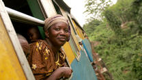 Congolese woman sticking head out of moving railroad car en route to market.