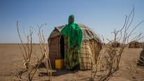 Woman stands in front of temporary shelter in drought-afflicted region.