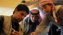 A volunteer from the International Rescue Committee holds a pen while two Syrian refugees point to an item on the page the volunteer is writing on.