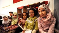 Five Syrian girls sitting in a school in Lebanon holding papers and pencils.