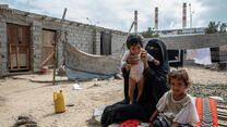 A mother and her two young children seated outdoors in Yemen