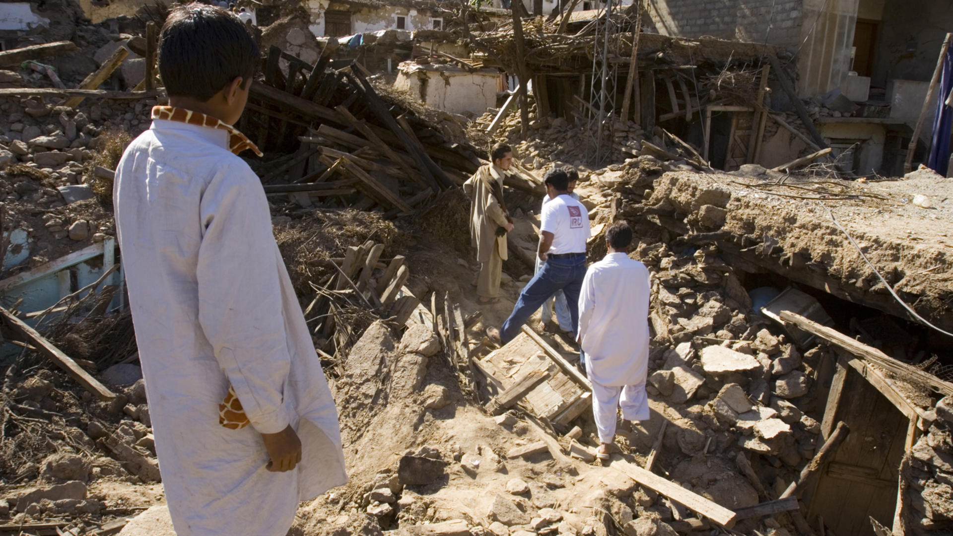 The IRC team had to hike over flattened houses and between precariously leaning walls to reach the village center.
