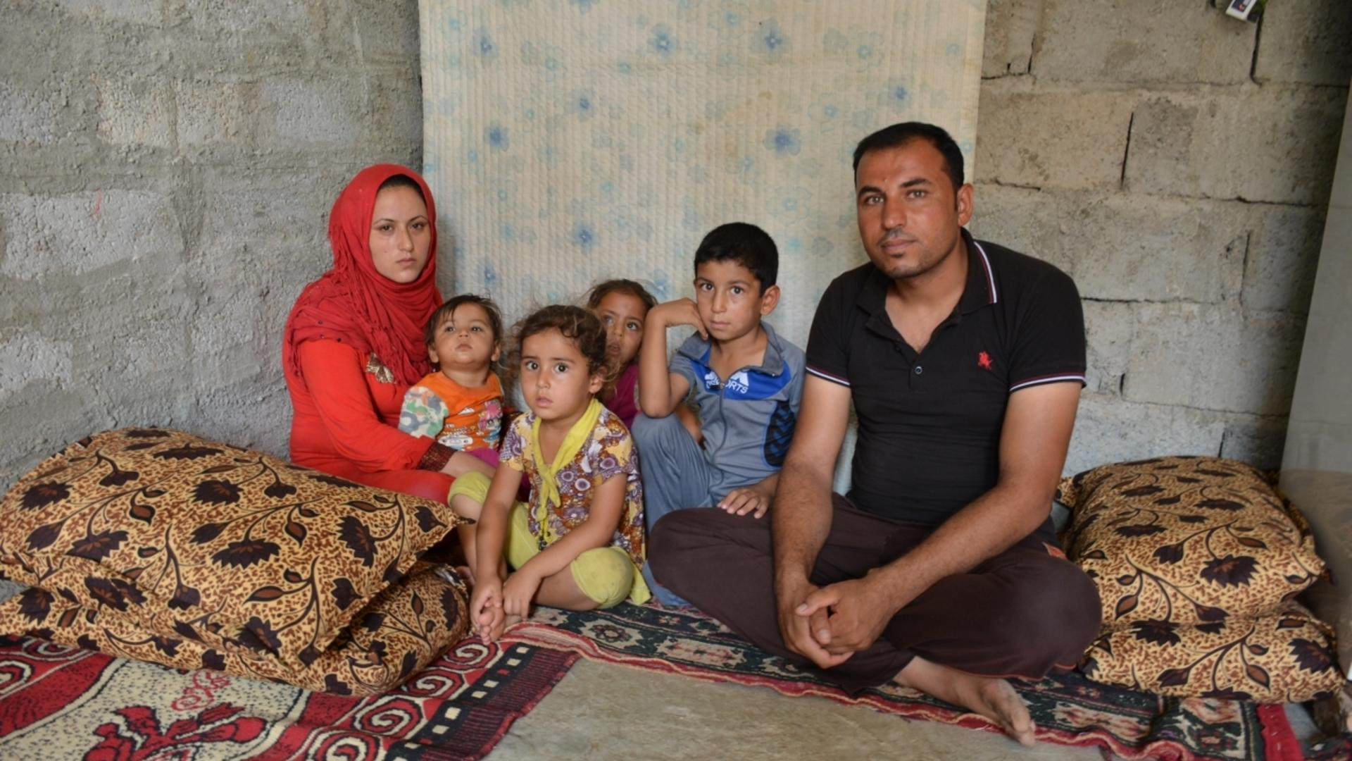 Naser and his family sit on cushions in a shelter after fleeing ISIS