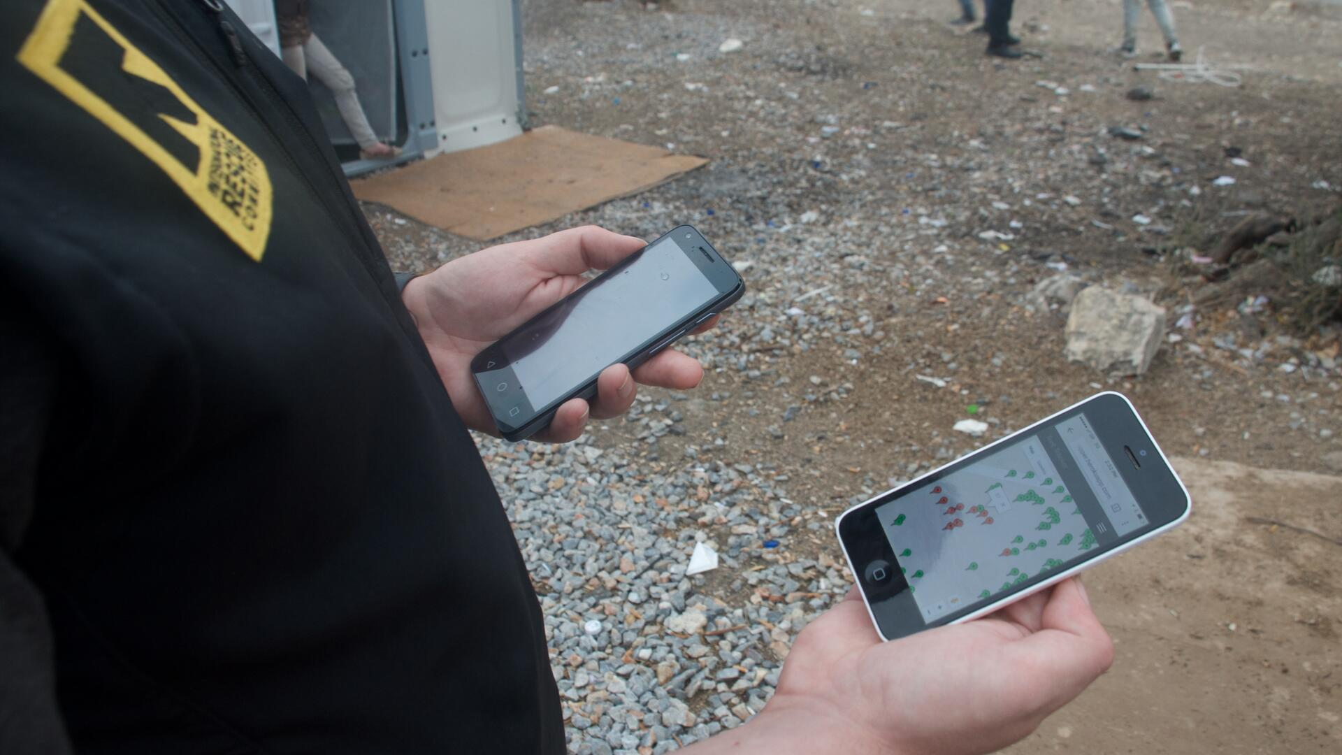 An IRC aid worker in Greece looks at an IRC  shelter mapping app on a smartphone