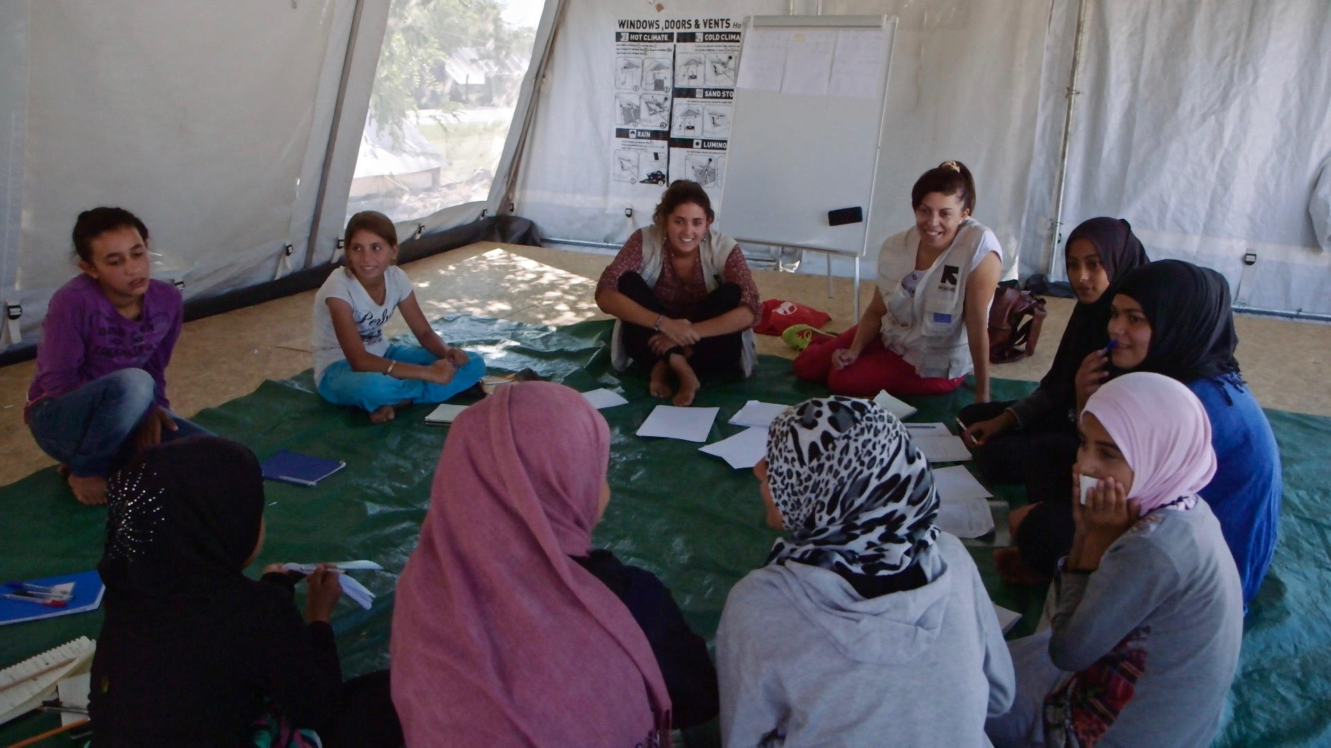 "Refugee girls play games in a tent that serves as an IRC ""safe space"" in a camp in Greece"