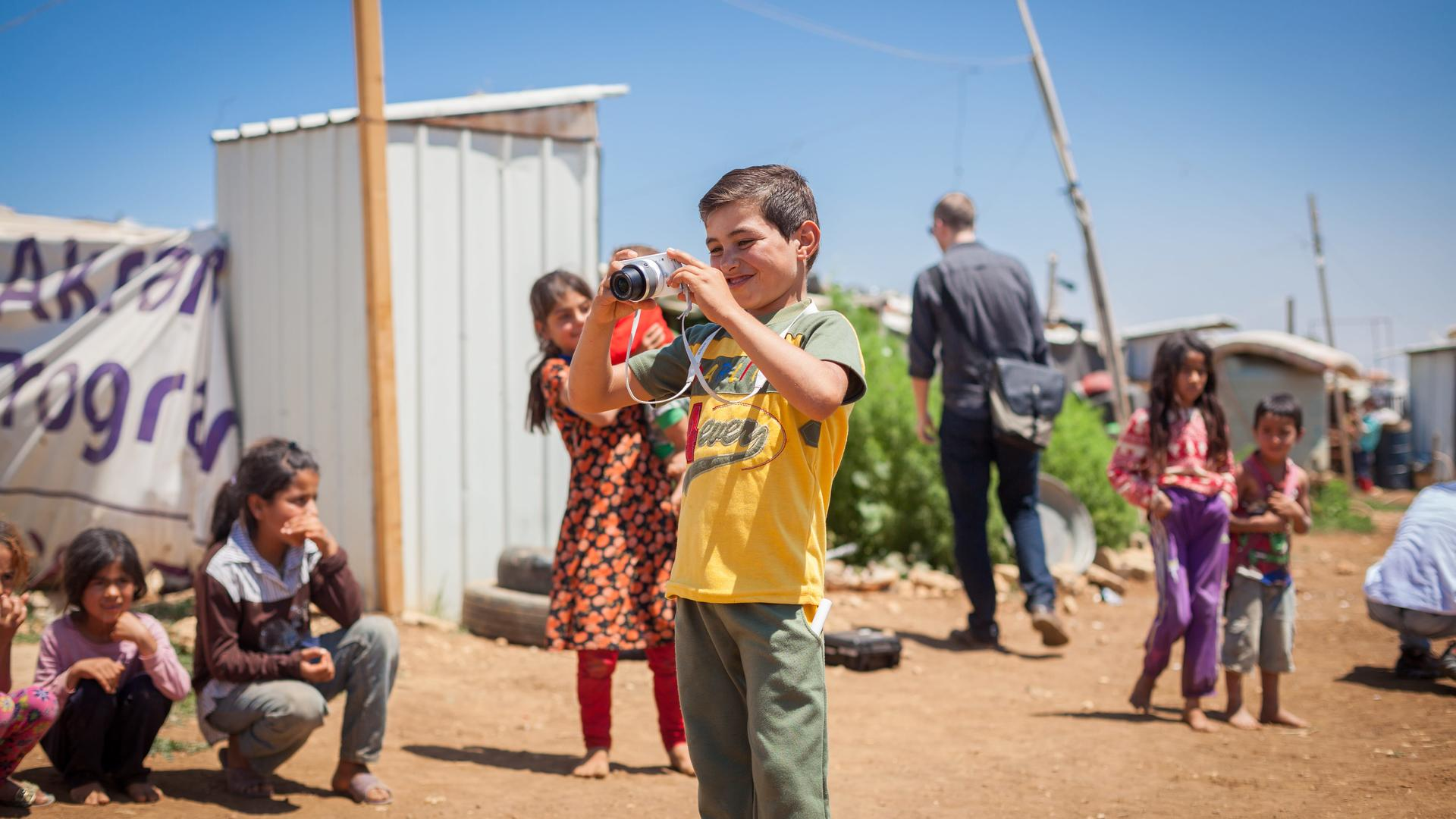 Maher, a Syrian boy, takes photographs of his friends in a refugee camp in Lebanon