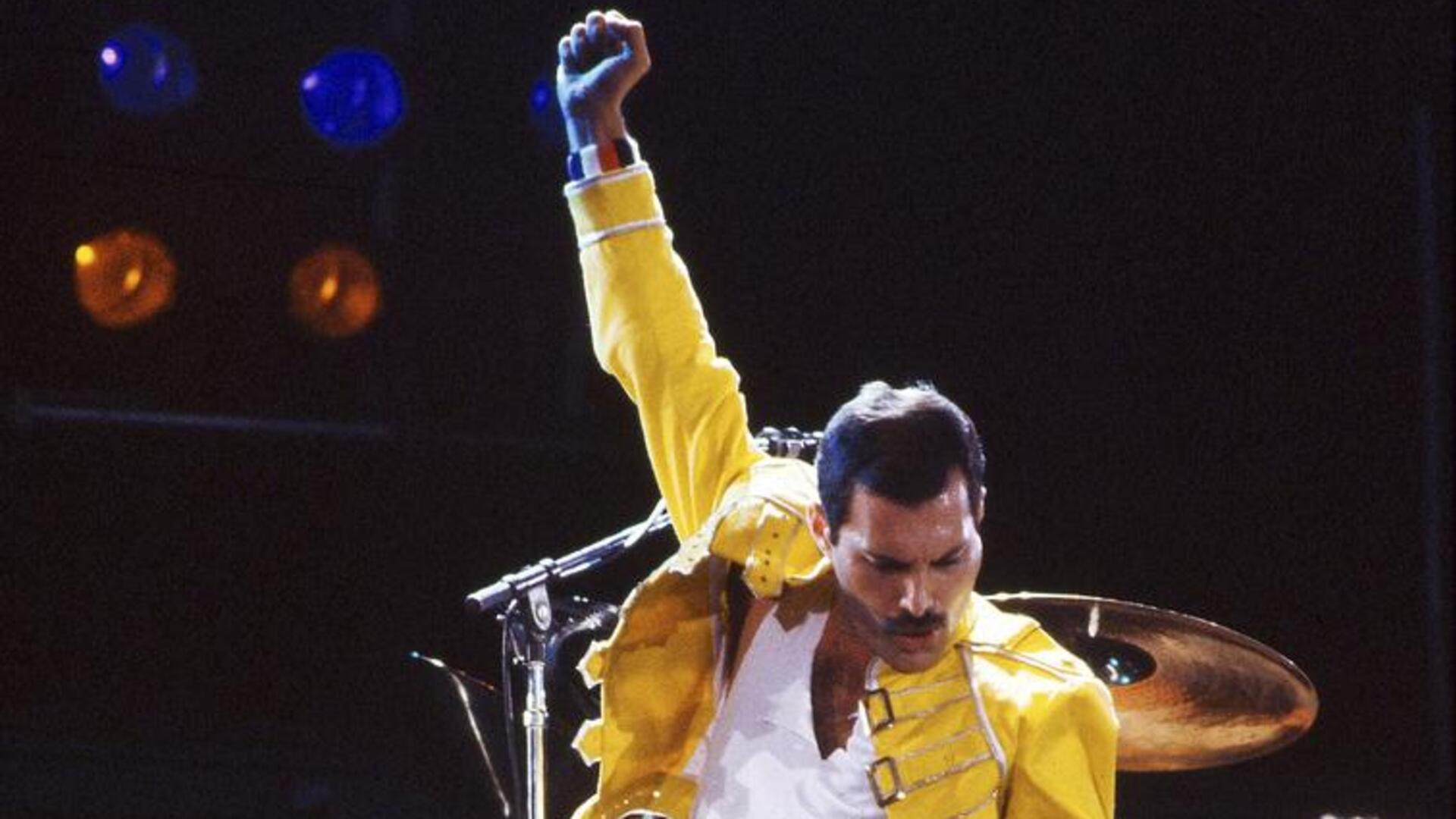 Freddie Mercury in performance, pumping his fist in the air