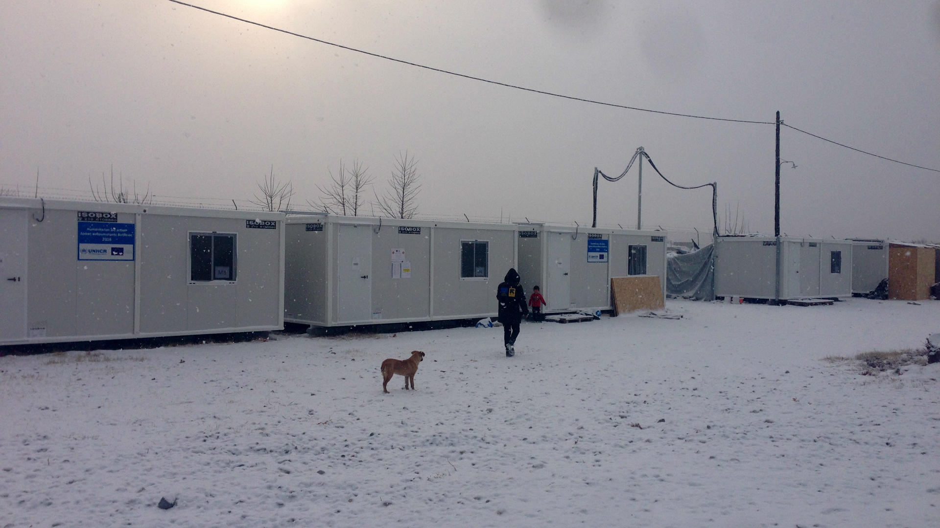 An IRc aid worker in a parka walks toward refugee shelters in Alexandria in the snow.