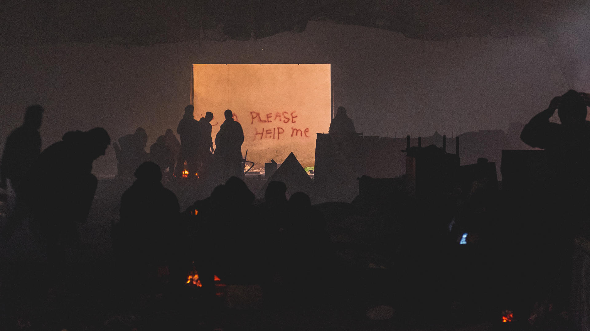 "Young refugees, seen in silhouette, warm themselves by a bonfire on a derelict industrial strip in Belgrade near graffiti that reads ""PLEASE HELP US."""
