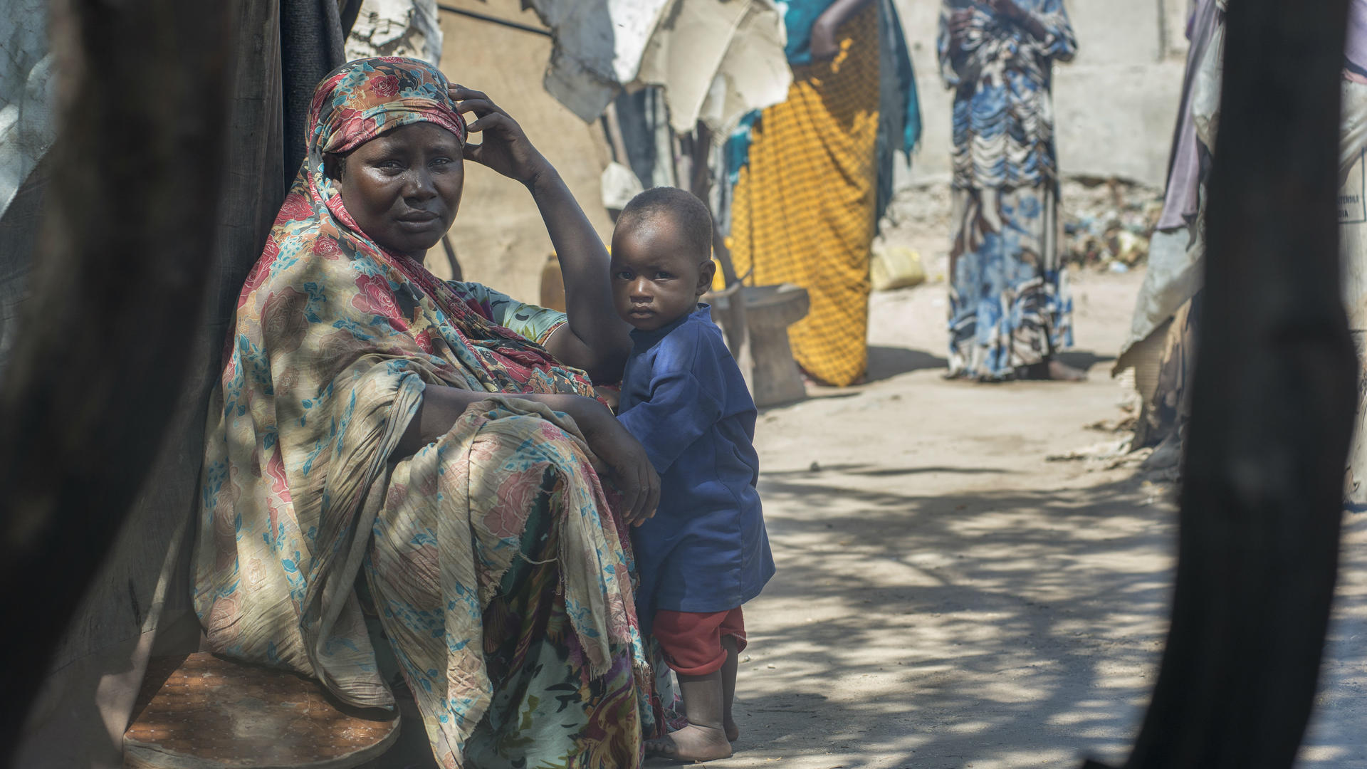 Displaced woman sits with a child outside a tent in Mogadishu