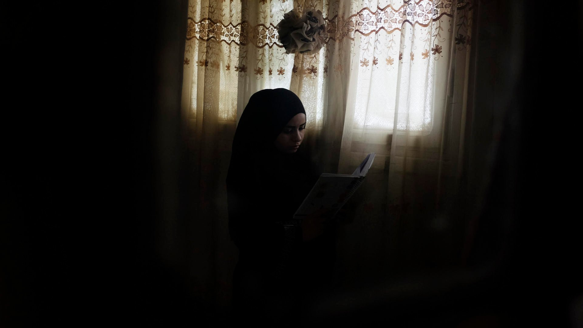 Rawan sits by a window, reading
