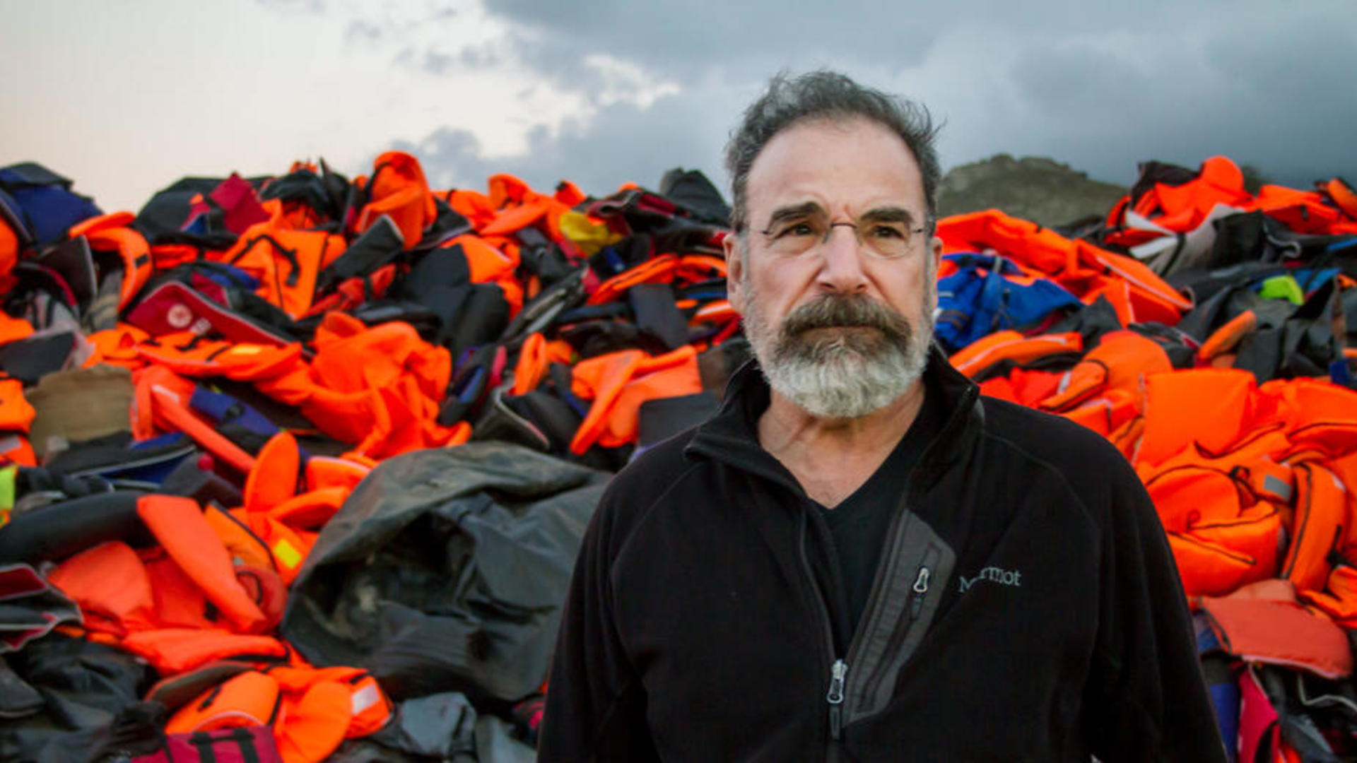 Mandy Patinkin in Greece, with a mountain of refugees' lifejackets