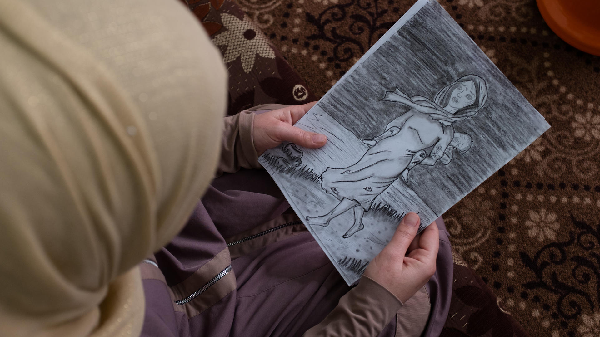 Syrian refugee woman holds a drawing