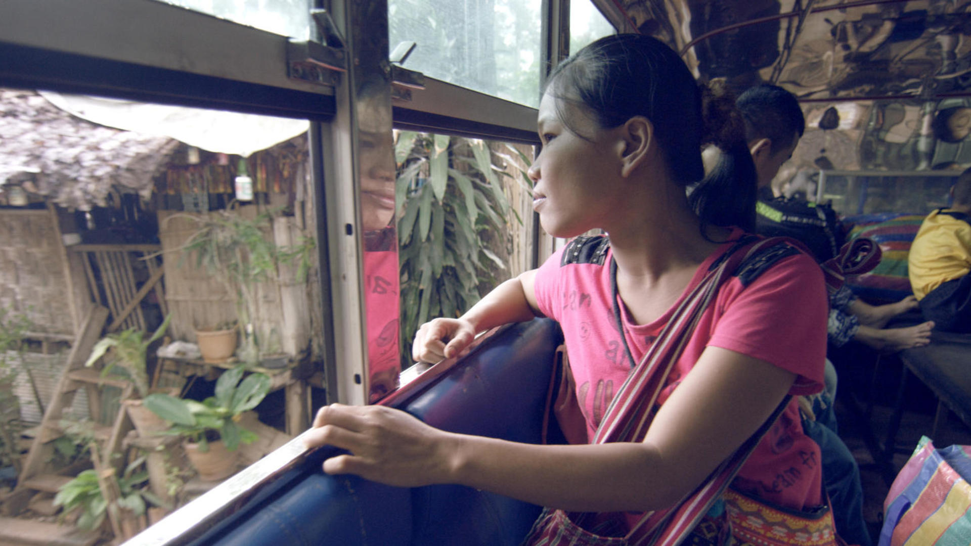 As a bus prepares to leave Mae La camp in Thailand, a Burmese woman looks out the window to say goodbye for the last time.