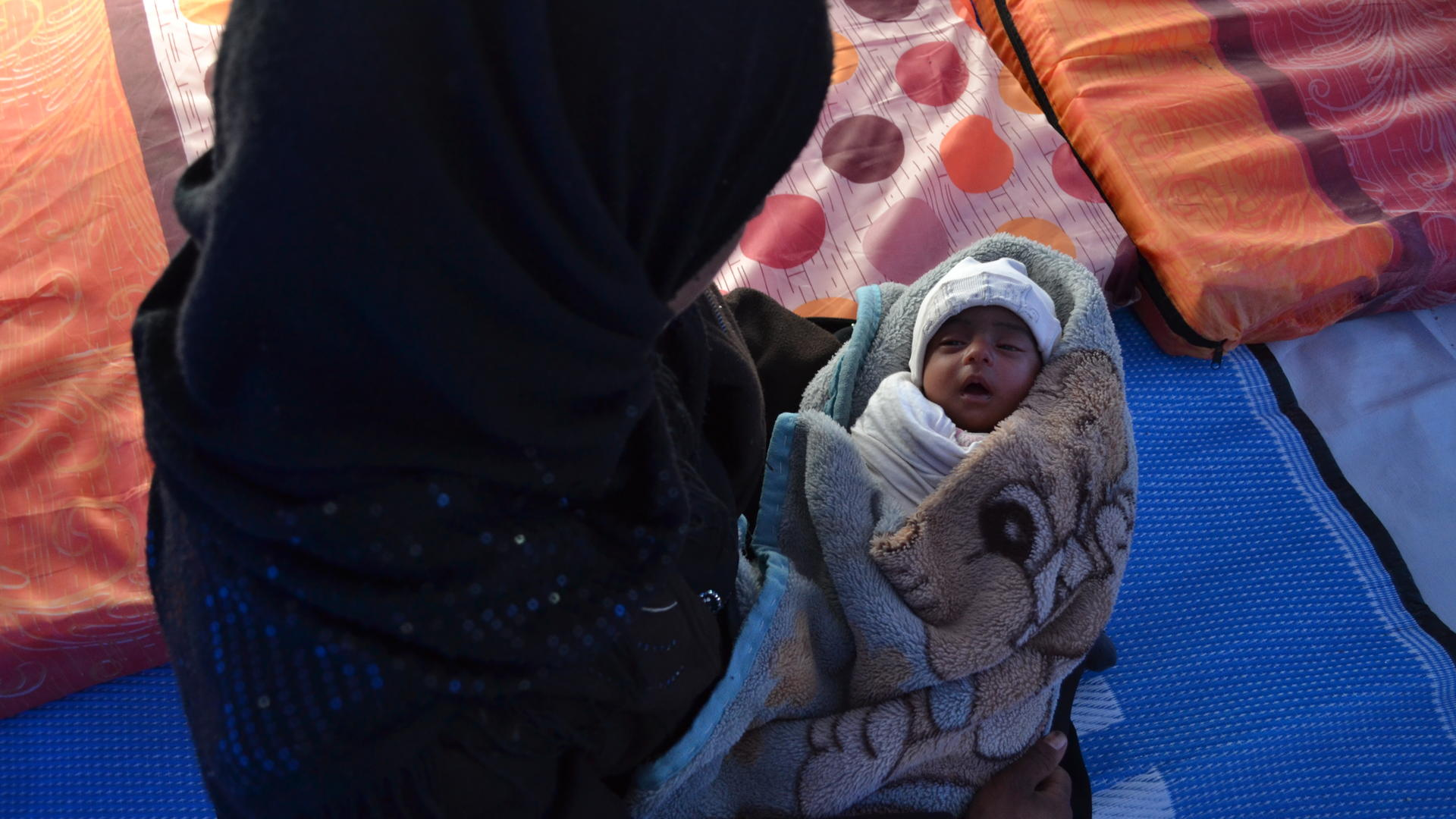 Alina and her infant daughter sit on the floor of a tent in a refugee camp in Iraq