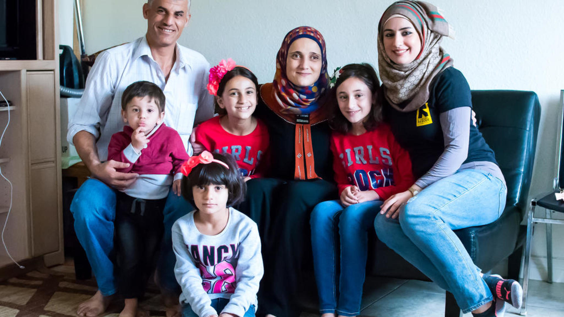The Tlas family, refugees from Syria, pose for a photo with an IRC staff member in their new home in San Diego