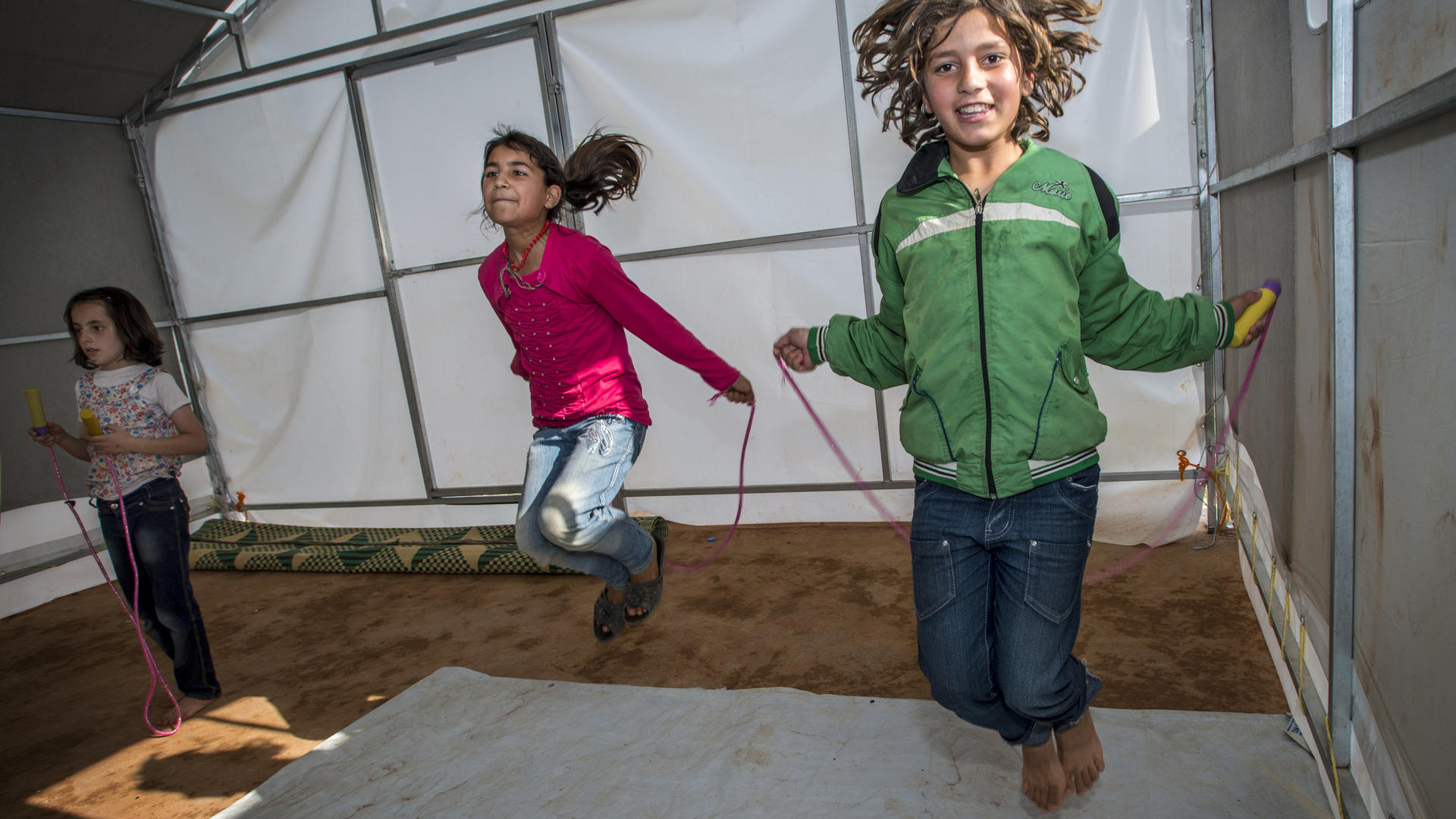 Two girls jump rope in a temporary classroom  in Idlib.
