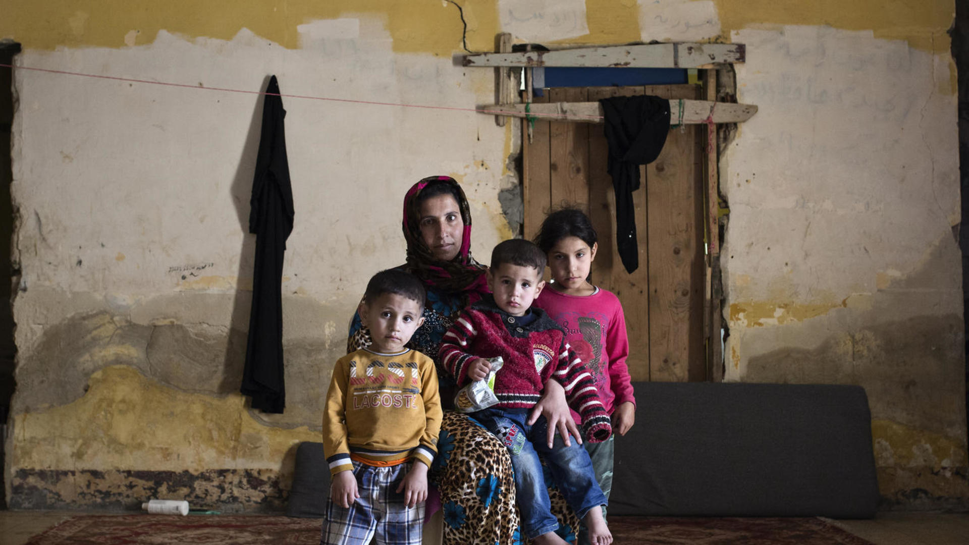 international committee irc a syrian mother and three children sit amid rubble in an abandoned building where they live