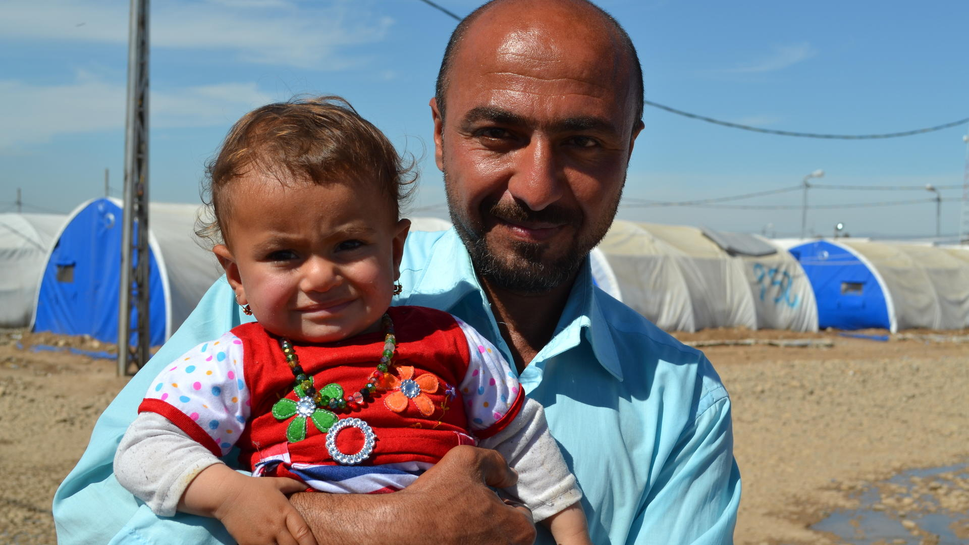Displaced Iraqi father with his baby daughter