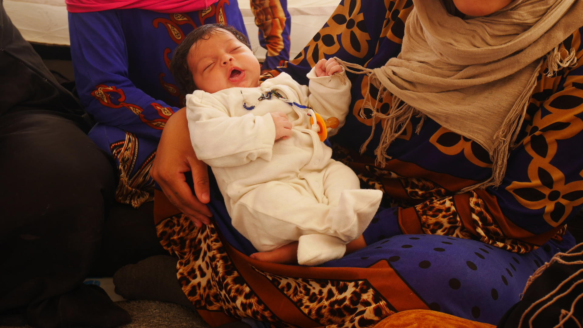 Three-week-old baby Ihab in his mother's arms inside a refugee tent