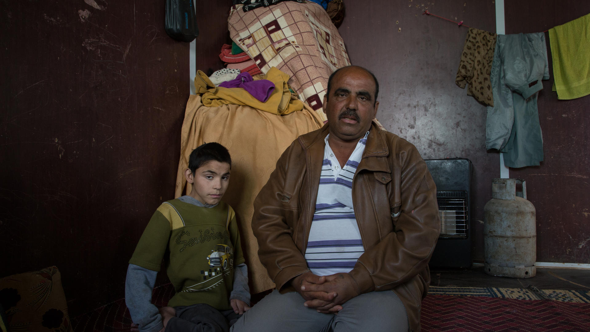 Abu Raed sits with his son Bashar, who is paralyzed, in their family's caravan at the Zaatari refugee camp in Jordan.