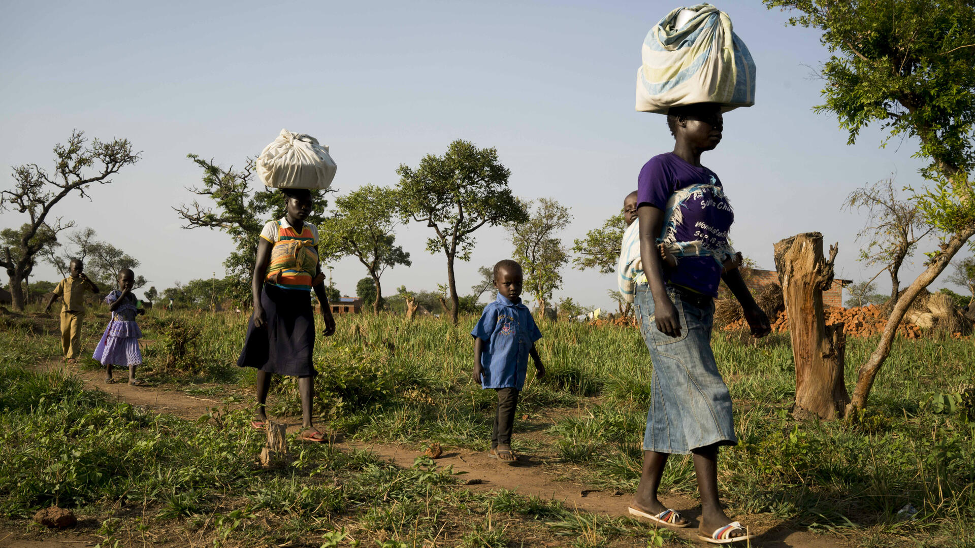 Women and their children arrive from Yei, South Sudan on foot, into the border town of Bosia,