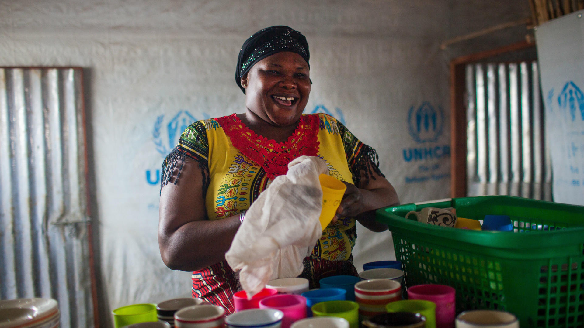 Zulu Likichio dries dishes at her restaurant in Bidi Bidi, Uganda
