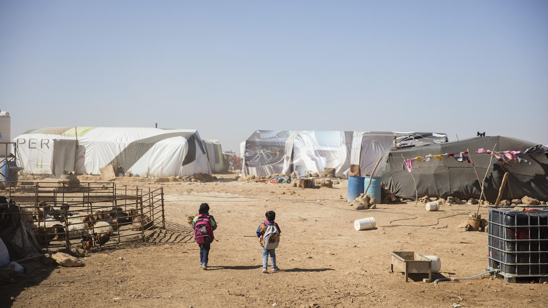 Syrian children walk through rows of tents in a refugee camp in Jordan