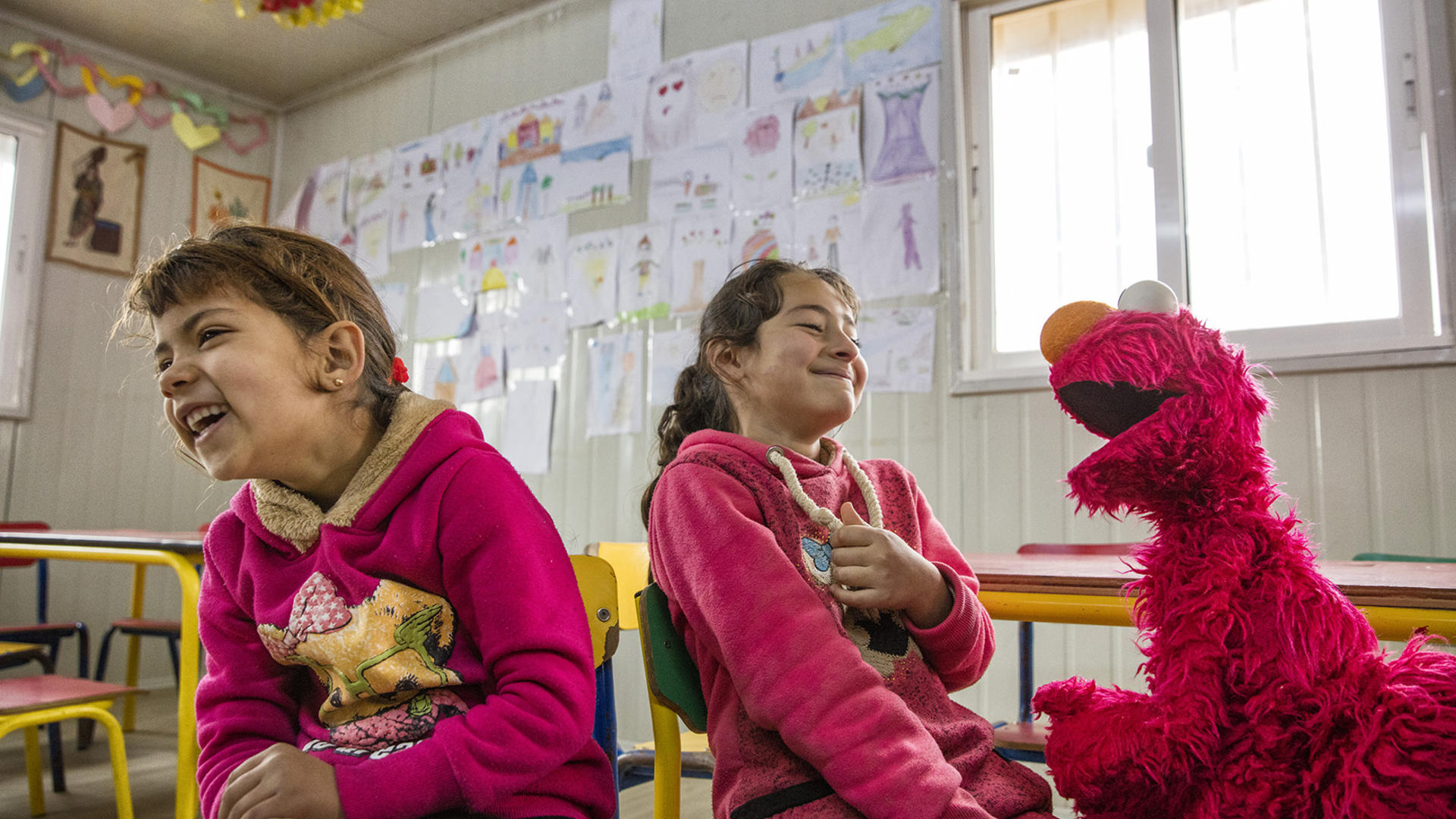 Elmo, the Sesame Street Muppet, makes two Syrian refugee girls laugh