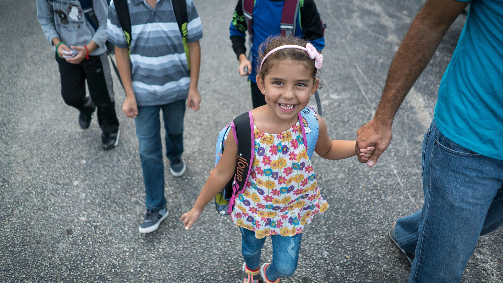 Jori holds her father's hand while walking to school