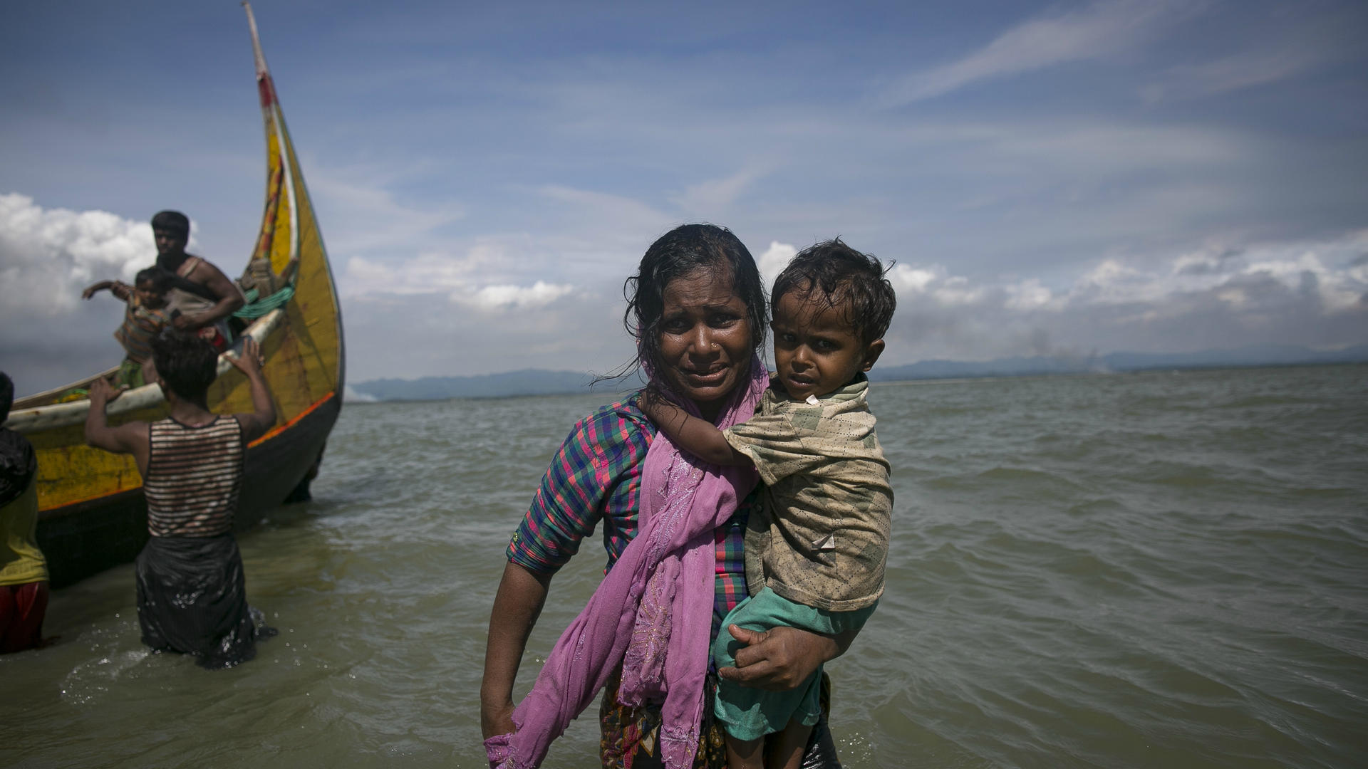 A Rohingya mother carries her child to shore after fleeing Myanmar's Rakhine State.