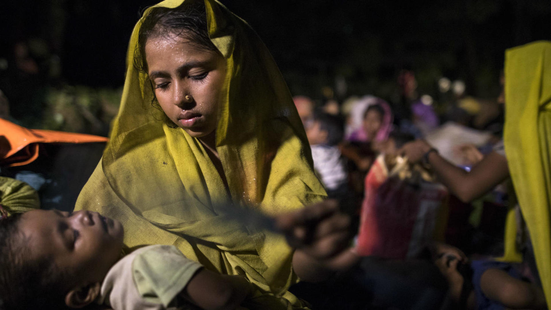 A Rohingya woman iholds her sleeping child