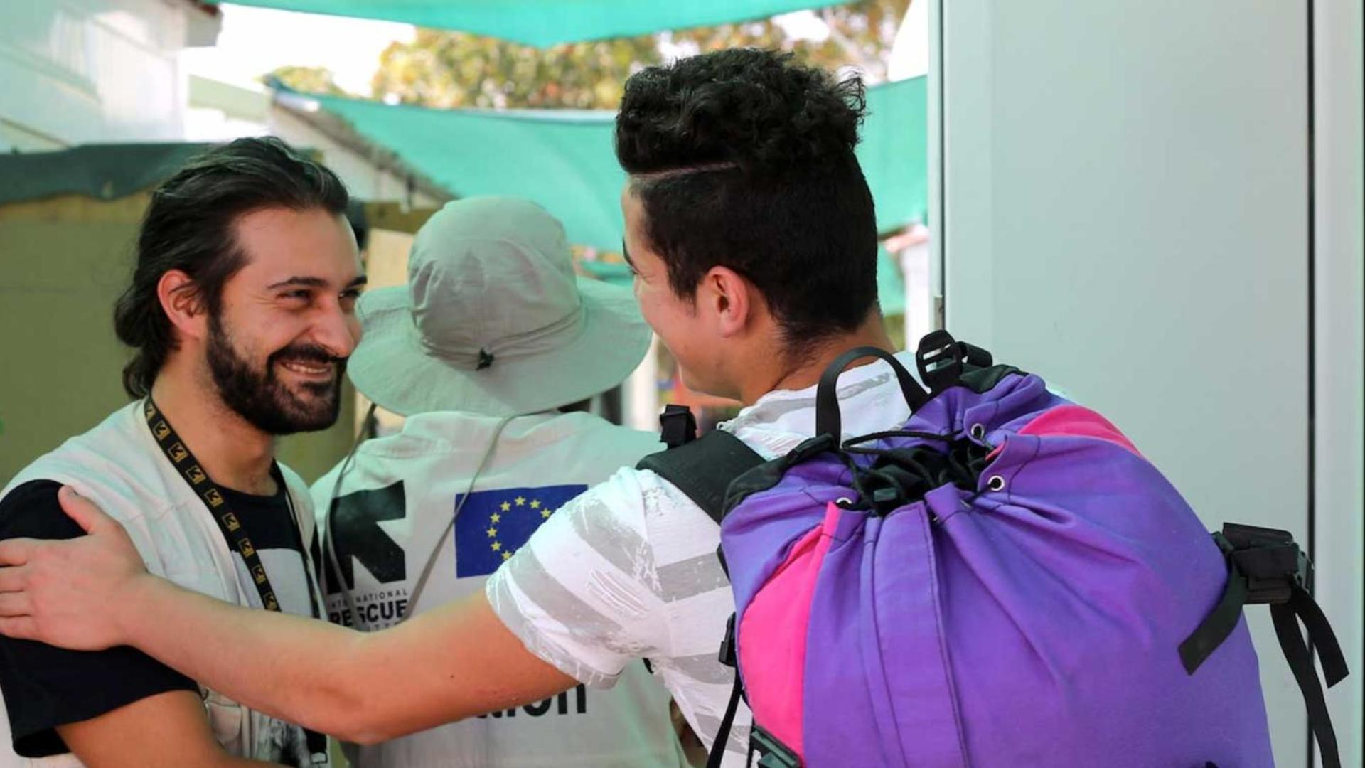 A young refugee in Greece says goodbye to an IRC aid worker as he leaves the camp to be reunited with relatives.