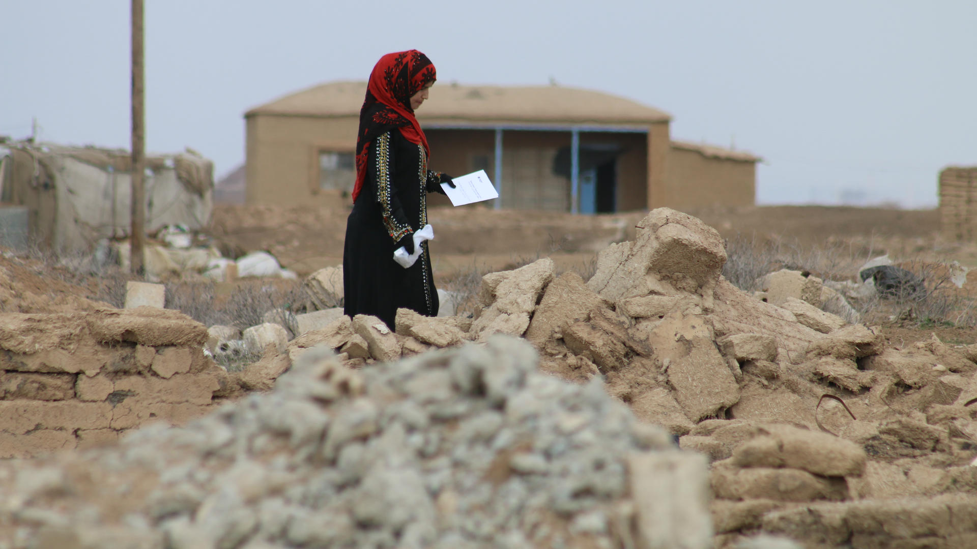 A woman picks her way through the rubble of her village in Northeast Syria.