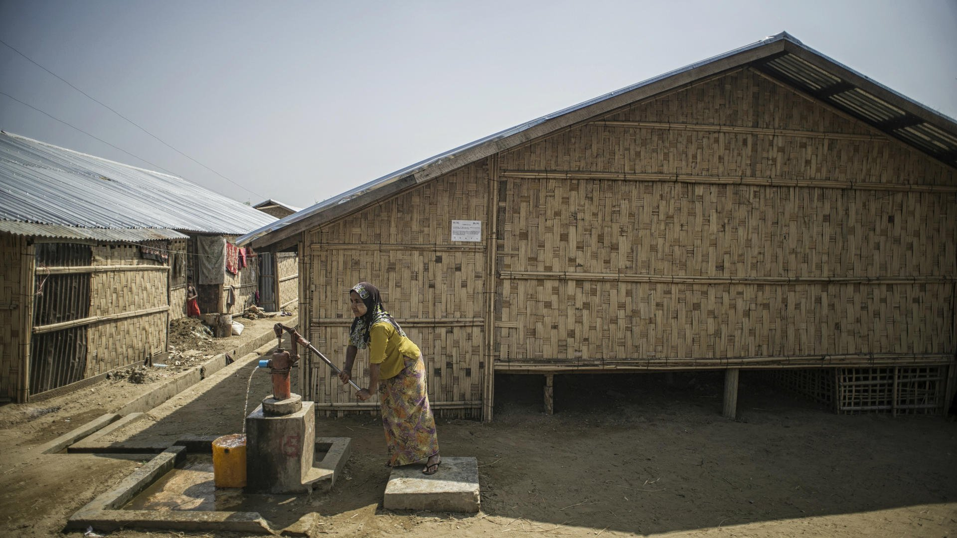 A Rohingya women pumps water outside a longhouse in Myanmar
