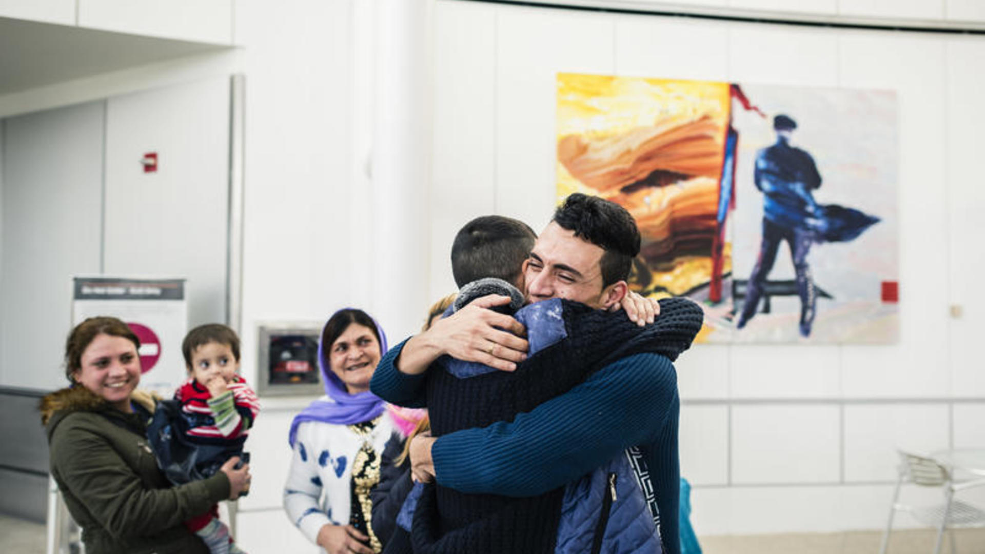 An Iraqi refugee hugs one of his relatives on arrival at a U.S. airport after being vetted for resettlement