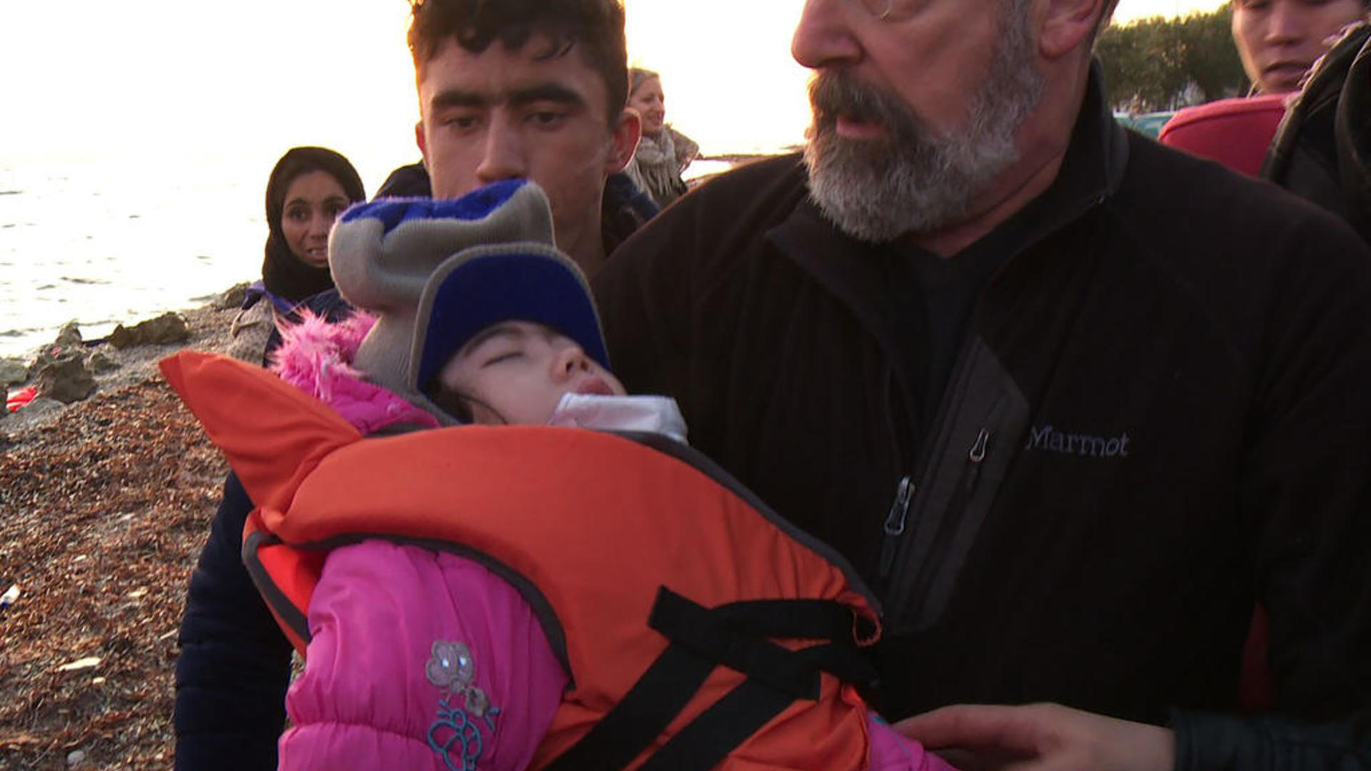 Mandy Patinkin carries Masuma, a young Afghan refugee onto a Greek beach
