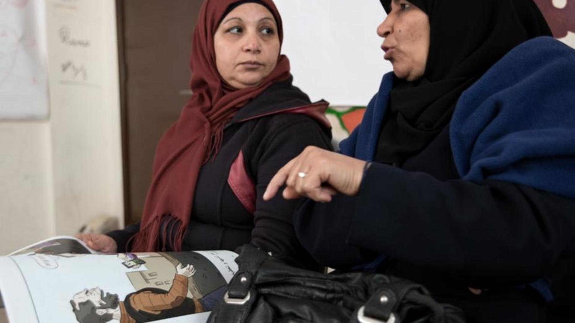 Syrian women look at an IRC-created comic book and discuss decisions the main character makes