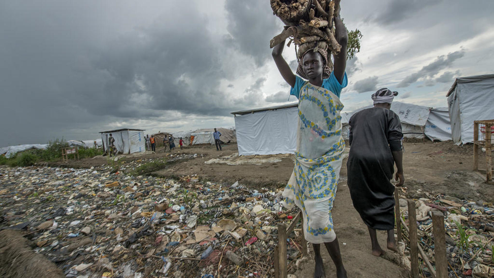 A woman carries firewood on her head in a camp for displaced people in South Sudan