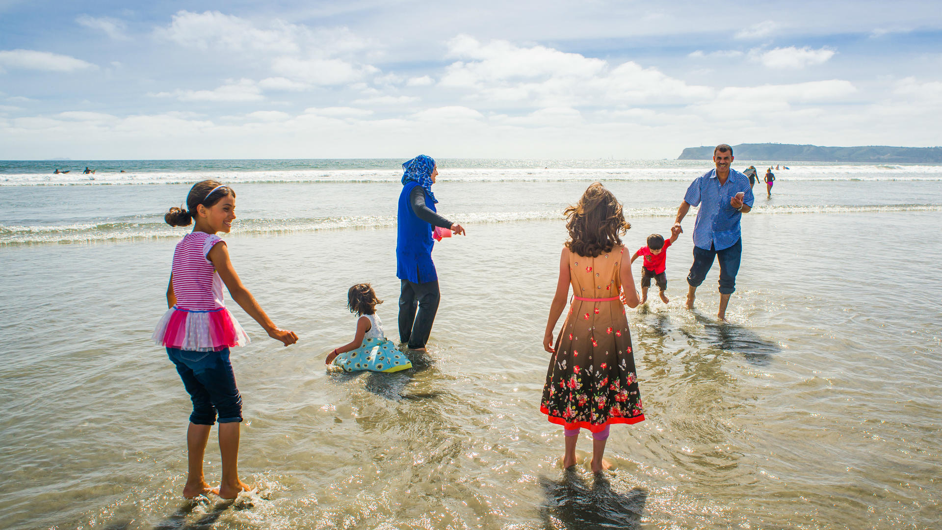 The Tlas family from Syria play in the surf at a California beach