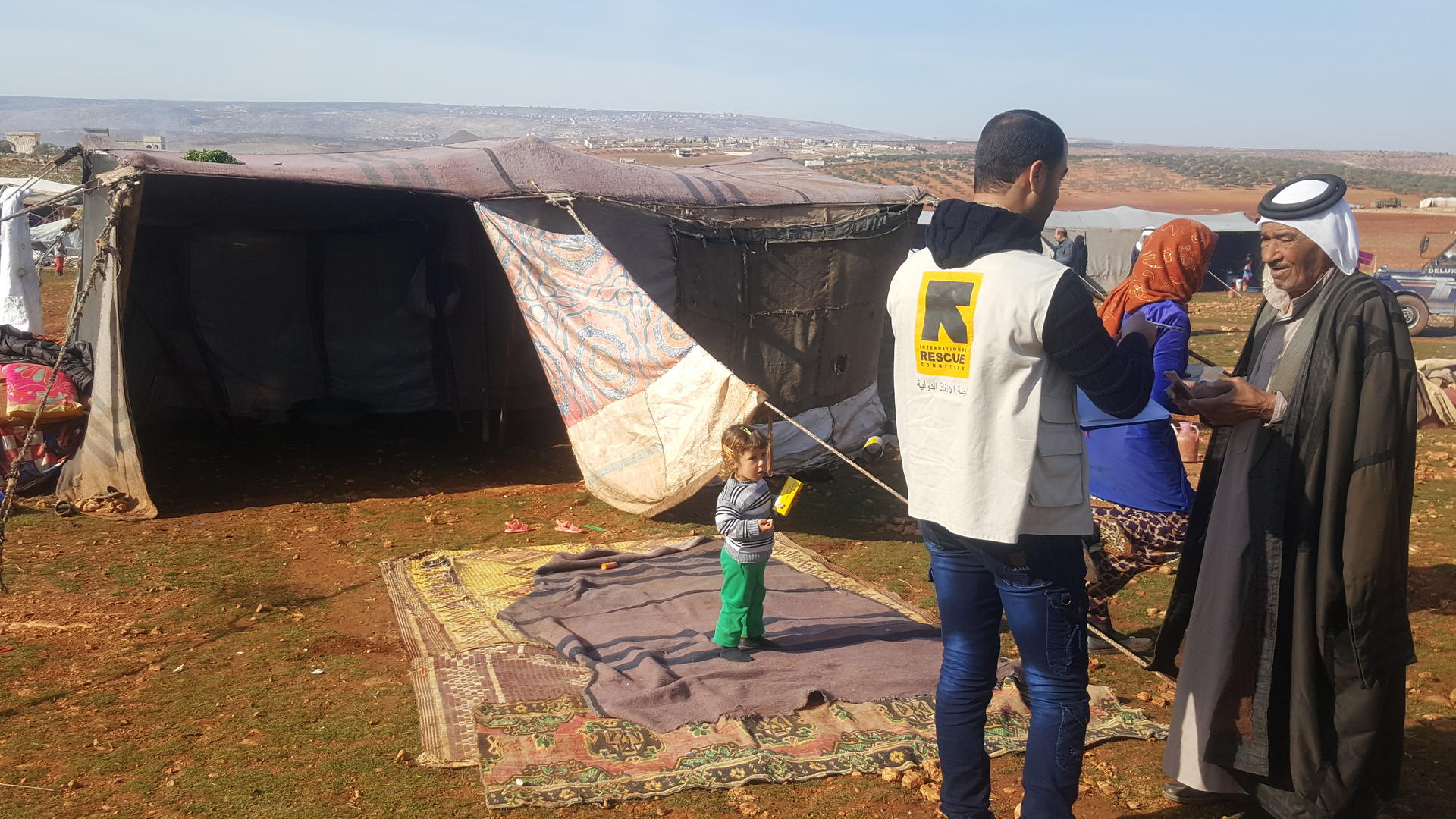 An aid worker speaks with a displaced Syrian man outside his family's tent