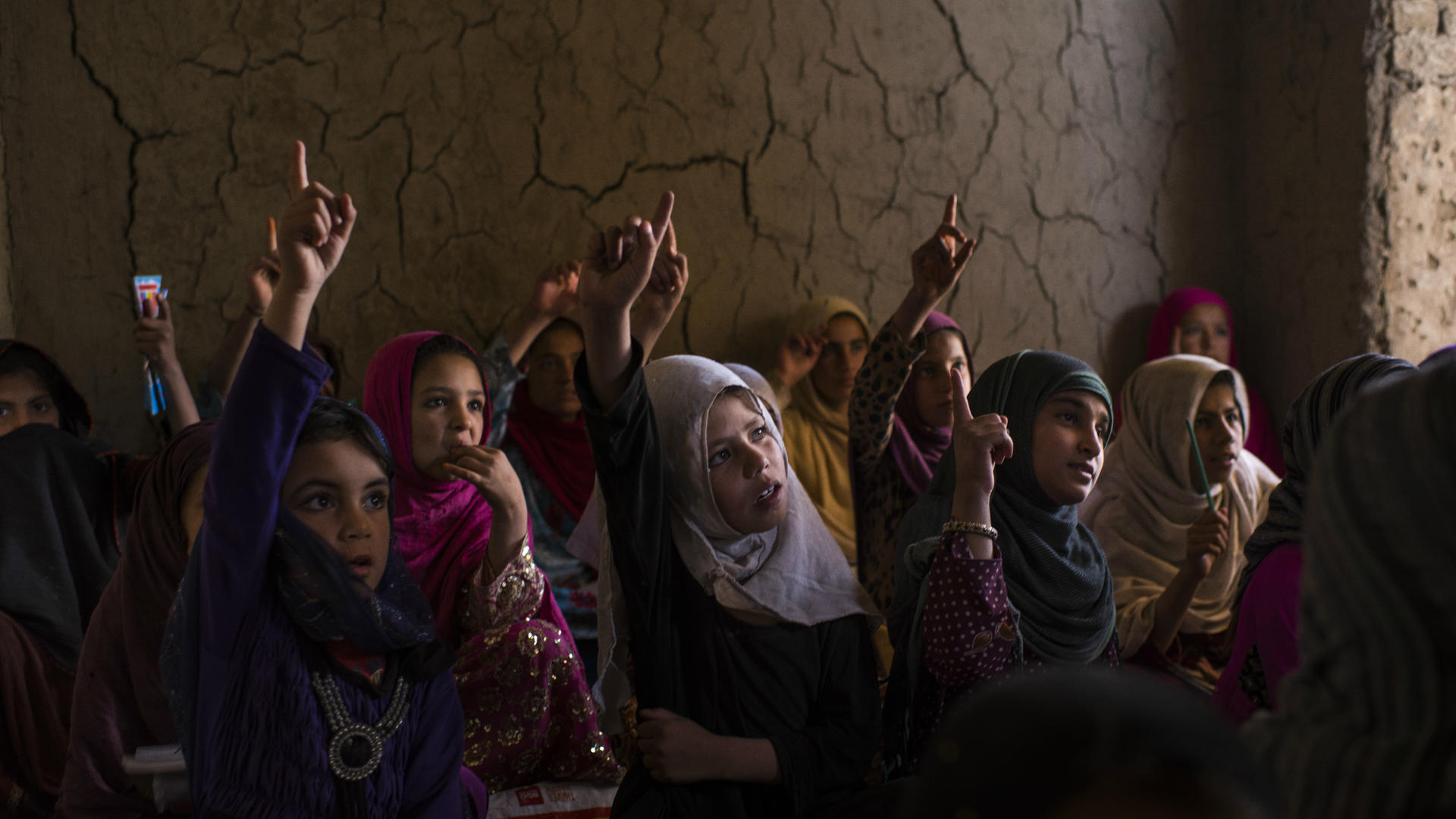 Girls raise their hands in a primary school classroom in Afghanistan