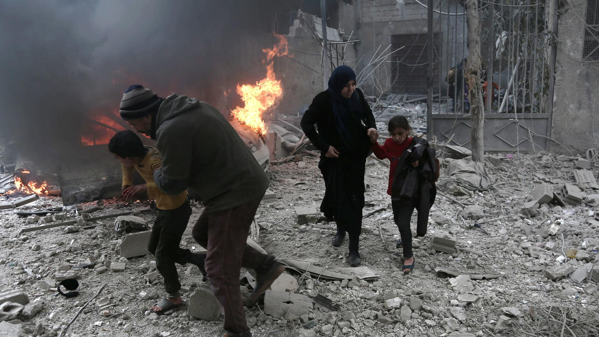 Syrian civilians run for cover from bombardment in Eastern Ghouta, Syria. Photo: Abdulmonam Eassa/AFP