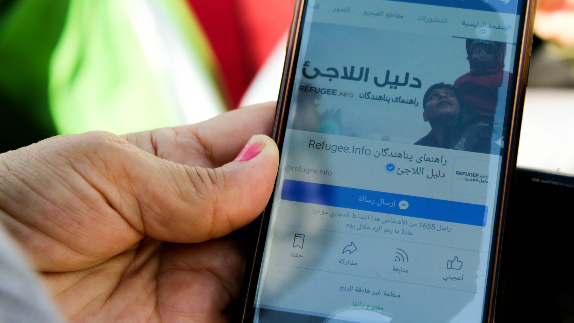 The Refugee.Info website shown on a mobile phone