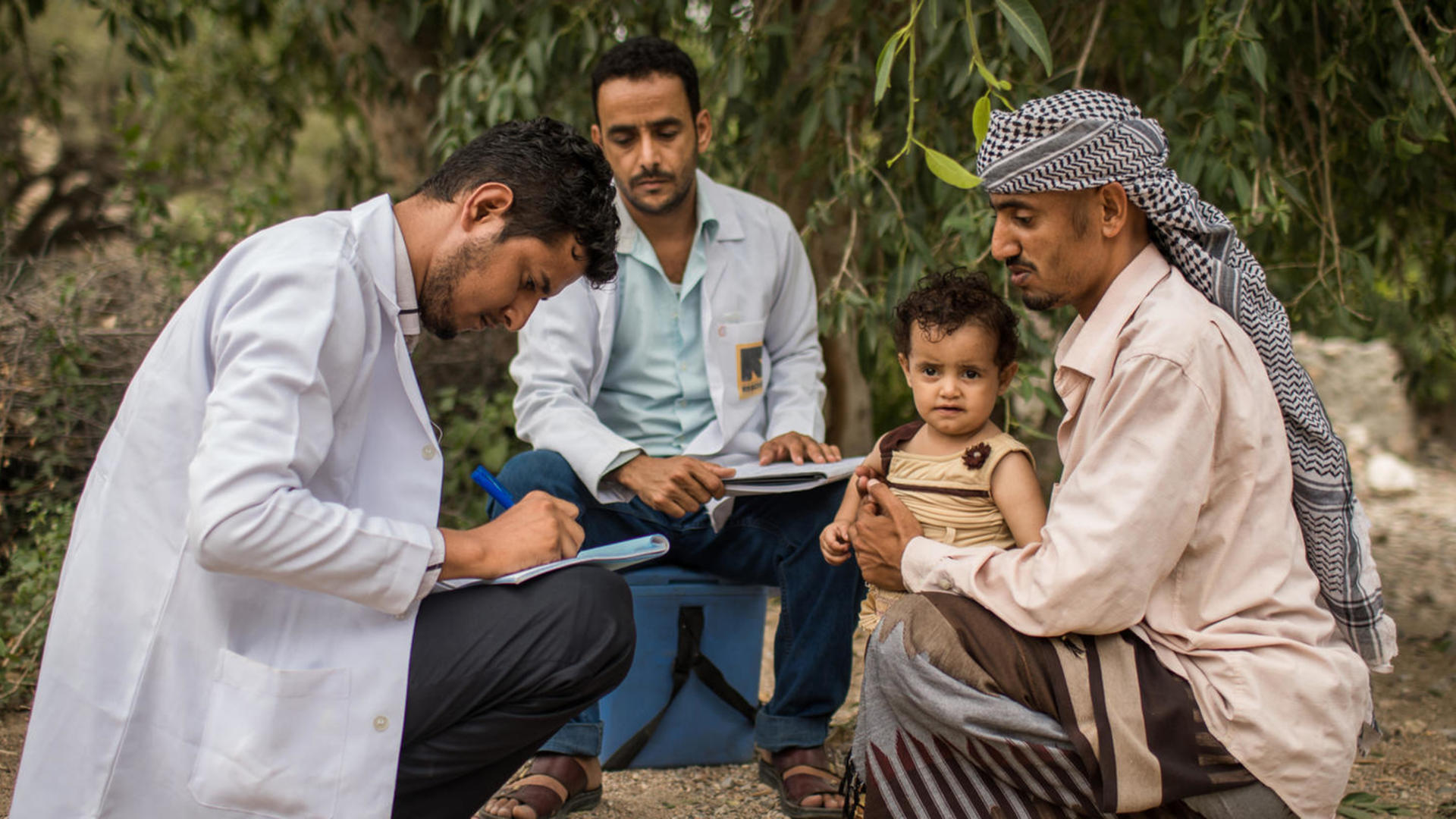 A health workers writes notes as he examines a child sitting on his father's lap