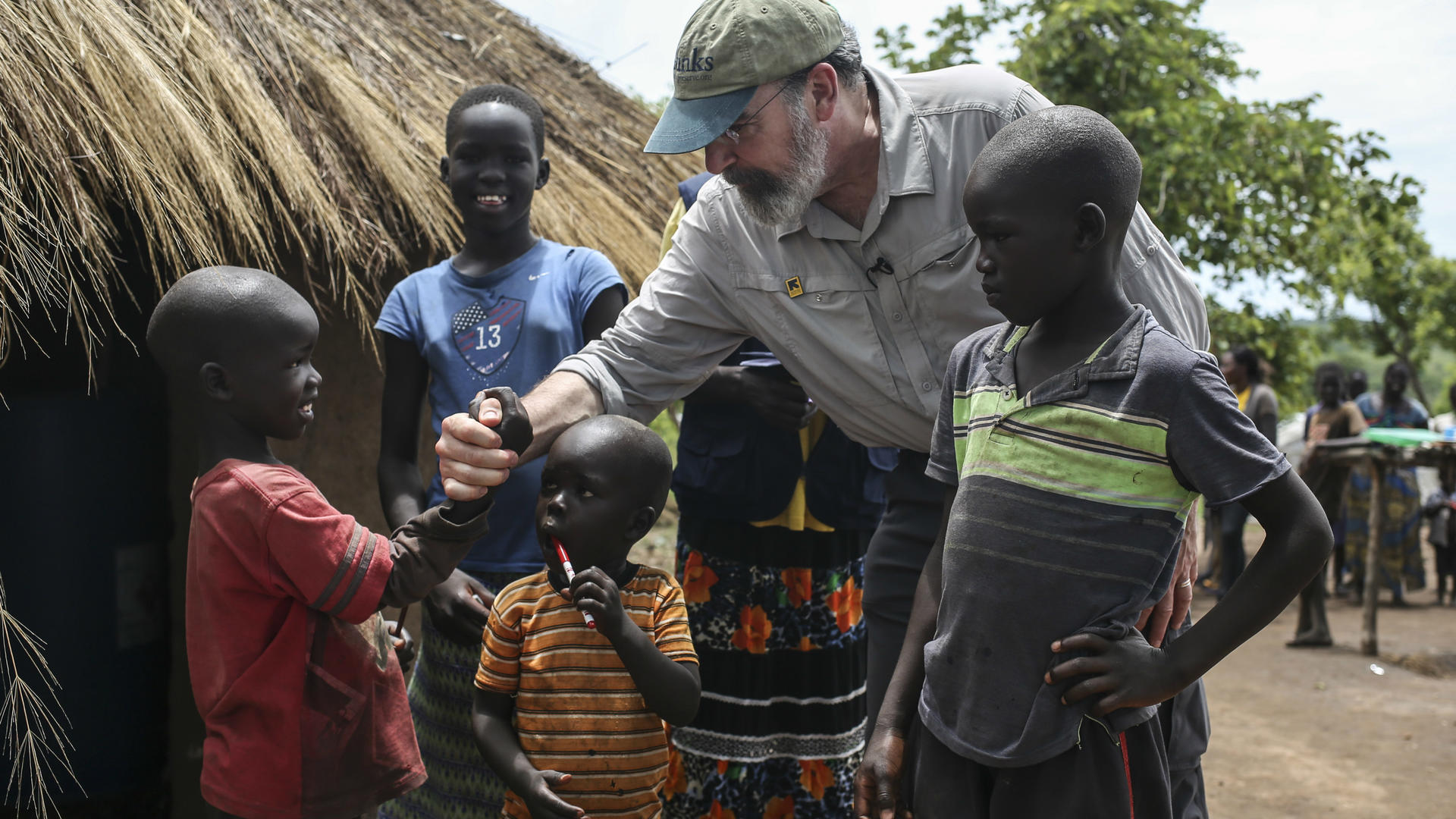 Mandy Patinkin with children at a refugee settlement in Uganda